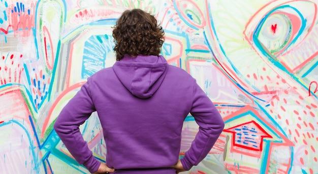Junger bärtiger verrückter mann, der verwirrt oder voll oder die zweifel und fragen sich wundert, mit den händen auf hüften, hintere ansicht gegen graffitiwand glaubt