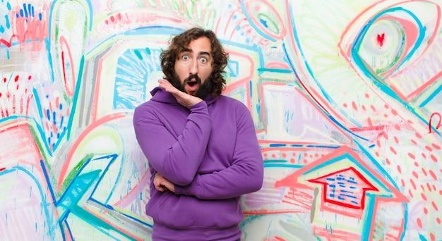 Junger bärtiger verrückter mann mit offenem mund vor schock und unglauben, mit gekreuzter hand auf wange und arm, der sich gegen graffiti benommen und erstaunt fühlt