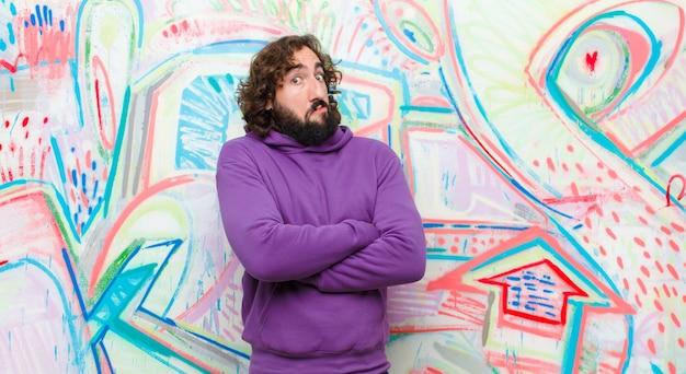 Junger bärtiger verrückter mann zuckt die achseln, fühlt sich verwirrt und unsicher und zweifelt mit verschränkten armen und verwirrtem blick gegen graffitiwand