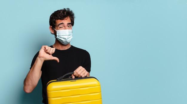 Junger bärtiger verrückter mit einer kovid-schutzmaske. reisekonzept