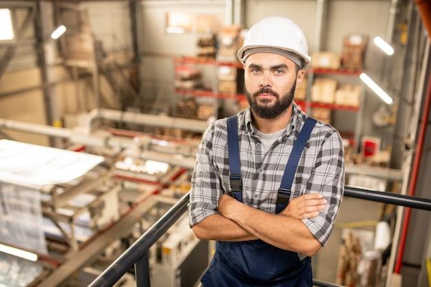 Junger bärtiger vorarbeiter in overalls und helm, der arme durch brust kreuzt, während er im lagerhaus der großen fabrik steht