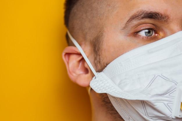 Junger bärtiger weißer mann mit einer medizinischen gesichtsmaske während der coronavirus-quarantäne. der vordere teil des gesichts war leicht verschwommen. coronavirus, covid-19-ausbruch. doktor, krankenschwester konzept.