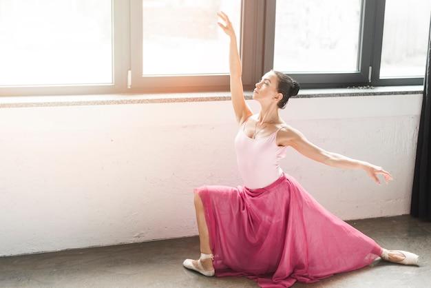 Junger balletttänzer, der nahe dem fenster aufwirft