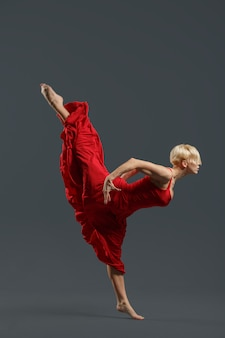 Junger balletttänzer, der rotes kleid trägt.