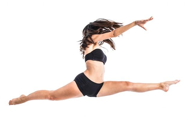 Junger balletttänzer, der über weißen hintergrund springt