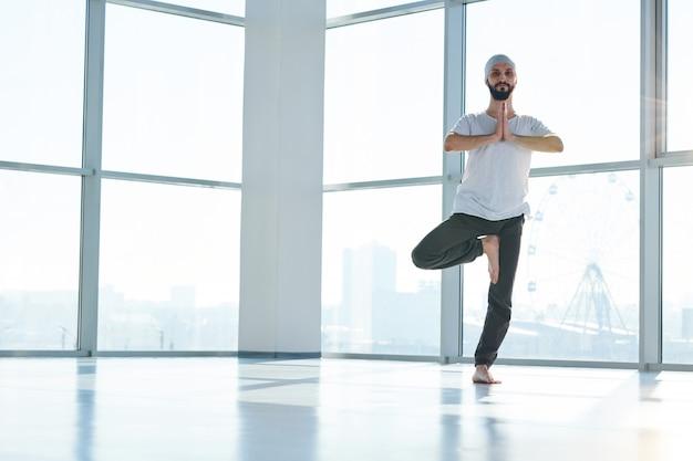 Junger barfußmann in aktivkleidung, der seine hände unter kinn zusammenhält, während er auf dem linken bein im fitnessstudio steht