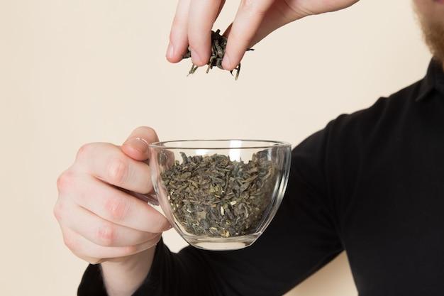 Junger barista, der getrockneten tee auf weißem boden einschenkt