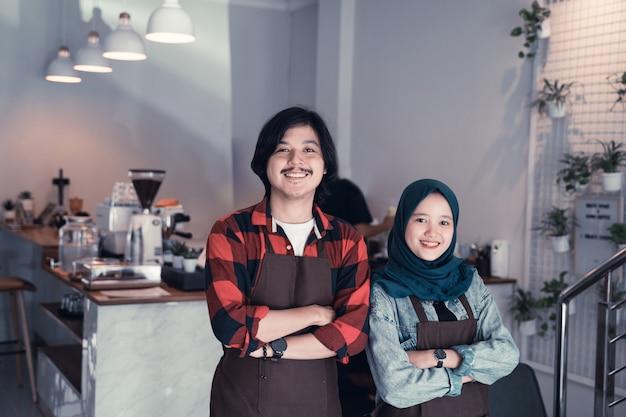 Junger barista, der zur kamera lächelt