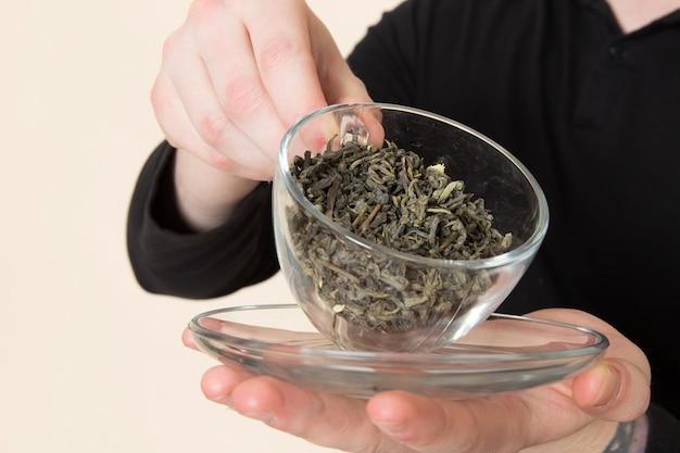 Junger barista hält ein glas mit getrocknetem tee auf dem schreibtisch