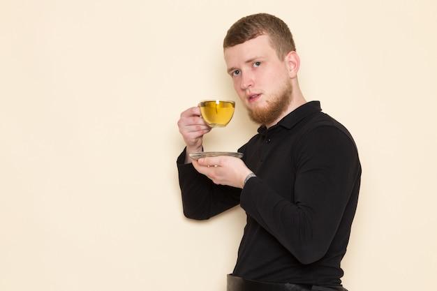 Junger barista im schwarzen anzug, der heißen grünen tee auf weißem schreibtisch trinkt