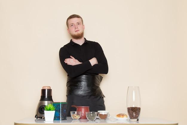Junger barista im schwarzen arbeitsanzug mit braunen kaffeesamen der zutaten und der kaffeeausrüstung auf weiß