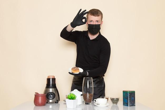 Junger barista im schwarzen arbeitsanzug mit zutaten und kaffeeausrüstung braune kaffeesamen, die schwarze sterile maske auf weiß tragen