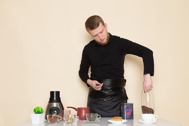 Junger barista im schwarzen arbeitsanzug mit zutaten und kaffeeausrüstung braune kaffeesamen machen einen kaffee auf weiß