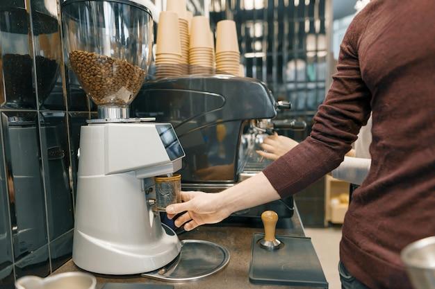 Junger barista mann, der einen espresso auf kaffeemaschine zubereitet