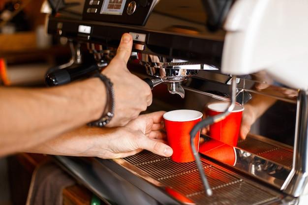 Junger barista-mann macht einen köstlichen kaffee in einer professionellen kaffeemaschine in einer roten pappbecher