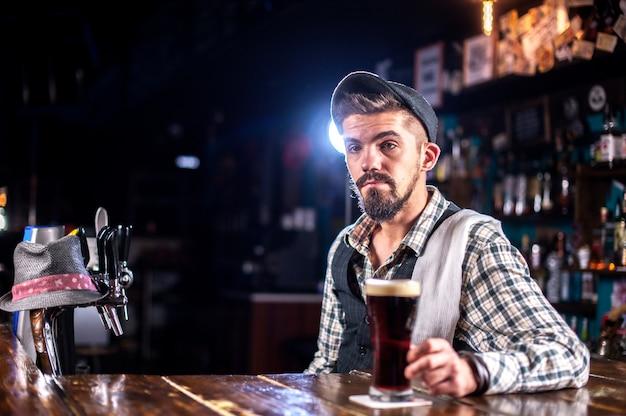Junger barkeeper, der einen cocktail in der kneipe kreiert