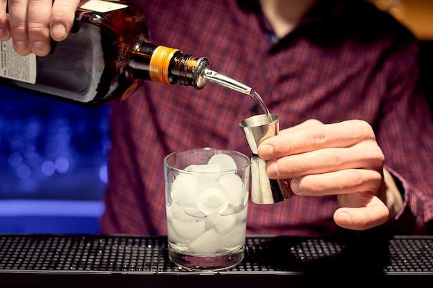 Junger barkeeper, der einen cocktail in einem glas mit eis vorbereitet und alkohol in einen jigger gießt.