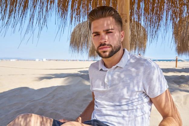 Junger bart mann in einem strand unter sonnenschirm