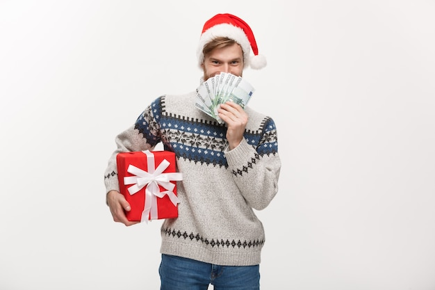 Junger bartmann, der eine weihnachtsgeschenkbox und geld auf weiß hält
