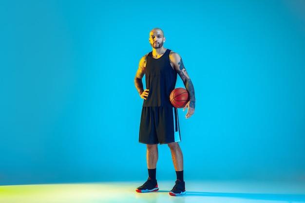 Junger basketballspieler des teams, das sportbekleidungstraining trägt, das in aktion übt, bewegung auf blauer wand im neonlicht