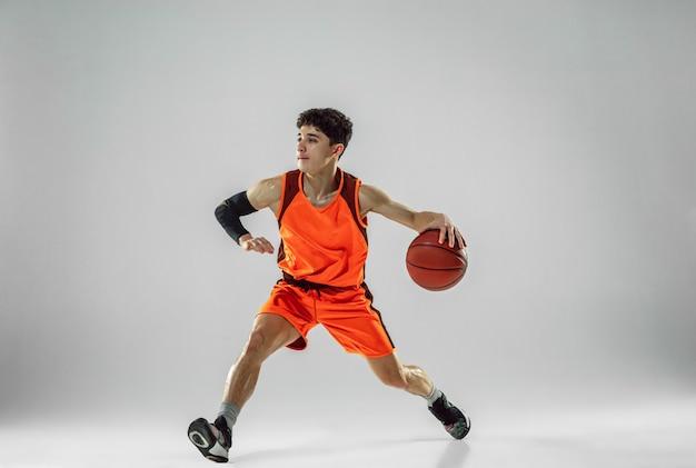 Junger basketballspieler des teams, das sportbekleidungstraining trägt, das in aktion übt, bewegung im lauf isoliert auf weißer wand