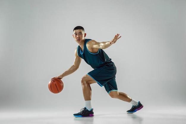 Junger basketballspieler des teams, das sportbekleidungstraining trägt, das in aktion übt, bewegung im lauf lokalisiert auf weißer wand. konzept von sport, bewegung, energie und dynamischem, gesundem lebensstil.