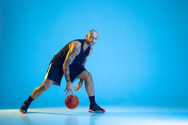 Junger basketballspieler des teams, das sportbekleidungstraining trägt, das in aktion übt, bewegung lokalisiert auf blauer wand im neonlicht. konzept von sport, bewegung, energie und dynamischem, gesundem lebensstil.