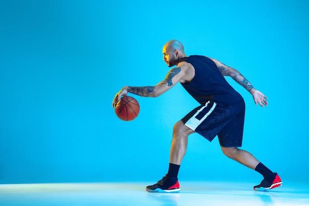 Junger basketballspieler des teams, das sportbekleidungstraining trägt, das in aktion übt, lokalisiert auf blauer wand im neonlicht