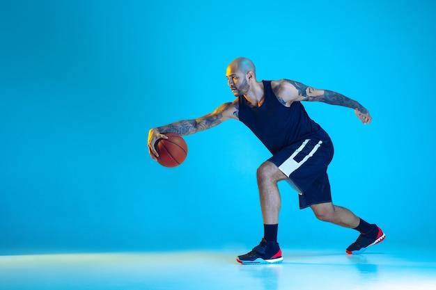 Junger basketballspieler des teams, das sportbekleidungstraining trägt, in aktion übt, bewegung einzeln auf blauem hintergrund im neonlicht. konzept von sport, bewegung, energie und dynamischem, gesundem lebensstil.