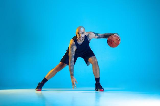 Junger basketballspieler des teams, das sportkleidungstraining trägt, das in aktion übt, bewegung lokalisiert auf blauem hintergrund im neonlicht. konzept von sport, bewegung, energie und dynamischem, gesundem lebensstil.