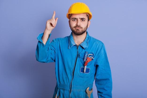 Junger bauarbeiter mit werkzeugen in der tasche, kleidet gelben helm und uniform nach oben