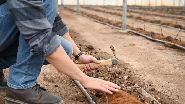 Junger bauer, der boden gräbt, um den boden für die aussaat vorzubereiten.
