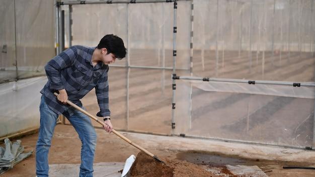 Junger bauer, der eine hacke verwendet, um erde und düngemittel für das pflanzen von gemüse zu schaufeln und zu mischen.