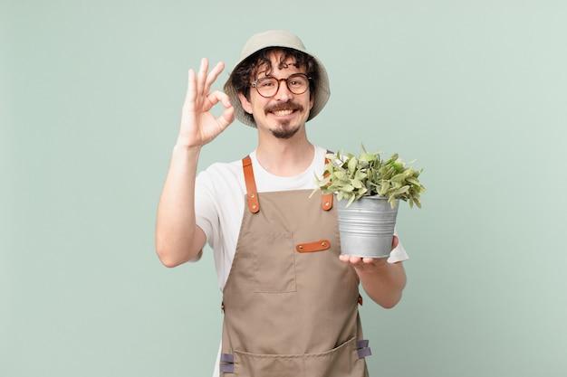 Junger bauermann, der sich glücklich fühlt und zustimmung mit okayer geste zeigt