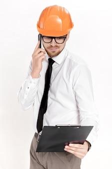 Junger bauingenieur im orangefarbenen helm mit ordner am telefon auf weißem hintergrund