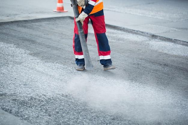 Junger baumeister auf asphaltierfertigermaschine während straßenstraßenreparaturarbeiten