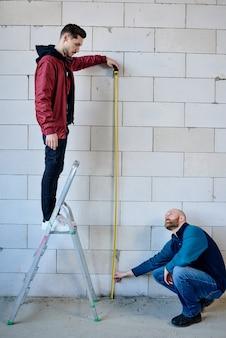 Junger baumeister, der auf trittleiter steht und maßband durch ziegelmauer hält, während sein kollege auf kniebeugen sitzt und sich mit ihm berät