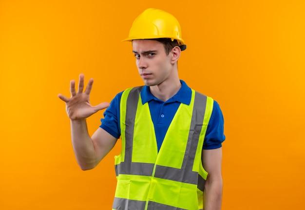 Junger baumeister, der bauuniform und schutzhelm trägt, erhebt nachdenklich die linke hand