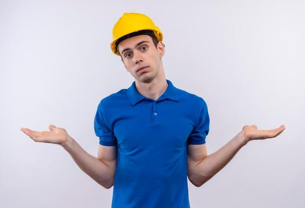 Junger baumeister, der bauuniform und schutzhelm trägt, weiß nicht, was zu tun ist