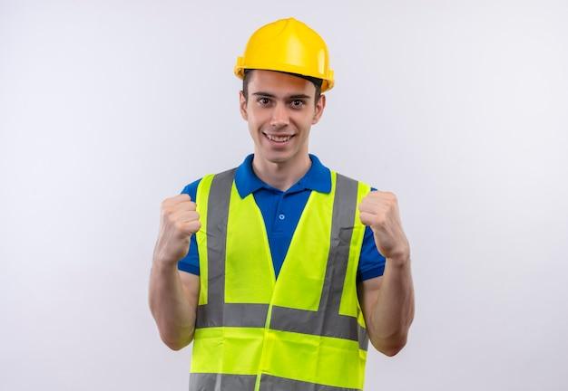 Junger baumeister, der bauuniform und schutzhelm trägt, zeigt glücklich macht mit fäusten