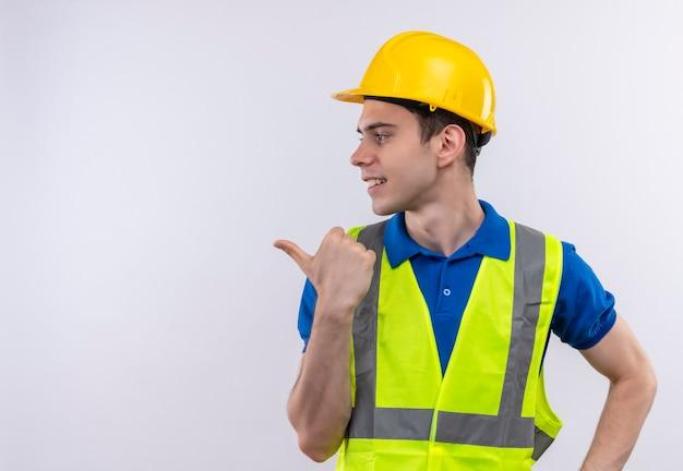 Junger baumeister, der bauuniform und sicherheitshelm trägt, zeigt mit zeigefinger nach rechts
