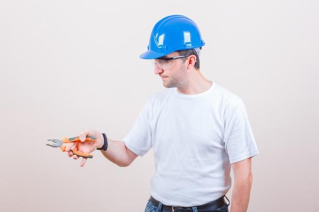 Junger baumeister, der eine zange in t-shirt, jeans, helm hält und selbstbewusst aussieht