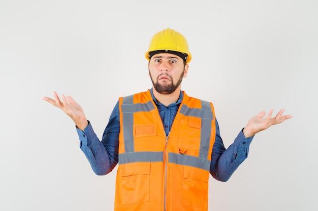 Junger baumeister, der hilflose geste in hemd, weste, helm zeigt und verwirrt aussieht. vorderansicht.