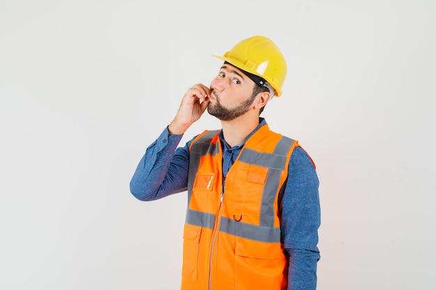 Junger baumeister, der reißverschlussgeste in hemd, weste, helm zeigt und vorsichtig schaut, vorderansicht.
