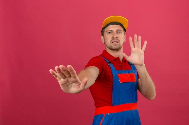 Junger baumeister in bauuniform und gelber kappe, die seine hände hochhält, die erzählen, kommen nicht näher über isolierte rosa wand