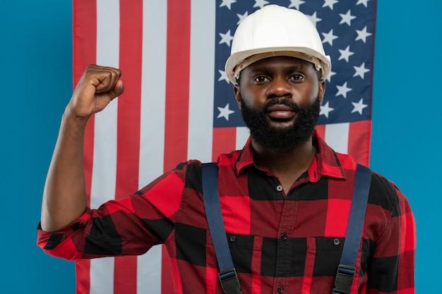 Junger baumeister oder vorarbeiter afrikanischer abstammung in arbeitskleidung und helm zeigt seinen starken arm im ellbogen gegen die amerikanische flagge