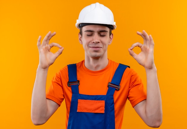 Junger baumeistermann, der bauuniform und schutzhelm trägt, der seine augen schließt und mit händen in ordnung tut