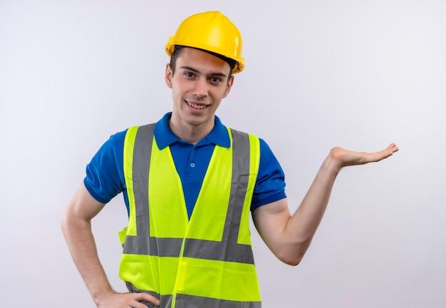 Junger baumeistermann, der bauuniform und schutzhelm trägt, lächelt und zeigt links mit der hand