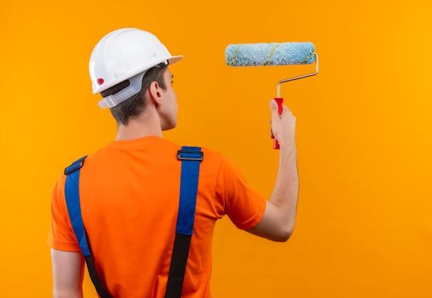Junger baumeistermann, der bauuniform und schutzhelm trägt, malt die wand mit einer walzenbürste