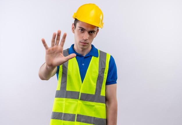 Junger baumeistermann, der bauuniform und schutzhelm trägt, stoppt ernsthaft mit hand